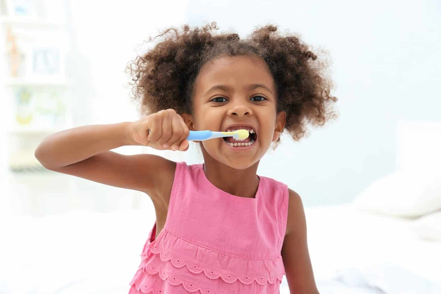 child brushing teeth with fluoride toothpaste