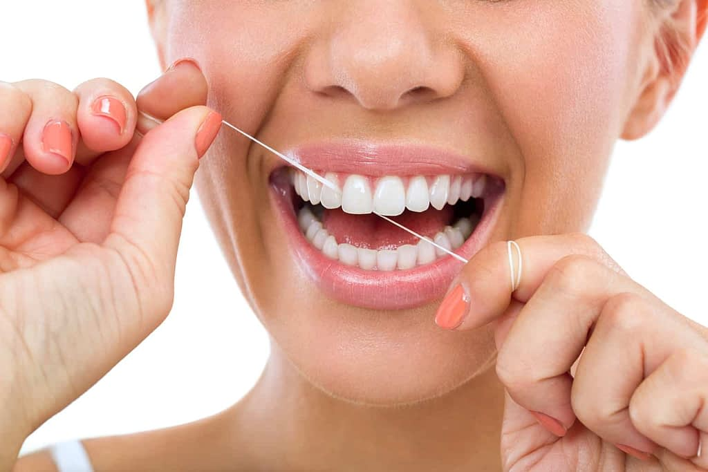 Lady flossing her teeth and smiling